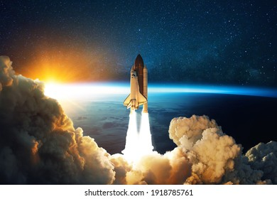 Rocket lift off. Space shuttle with smoke and blast takes off into space on a background of blue planet earth with amazing sunset. Successful start of a space mission. Travel to Mars