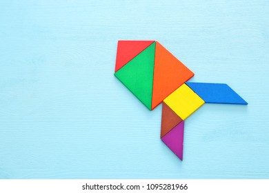 rocket made from tangram puzzle on blue pastel wooden background