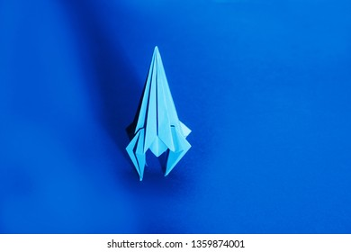 rocket from paper of origami on a blue background