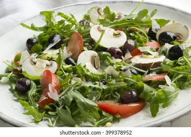Rocket salad with Champions, tomatoes and Olives on a Plate
