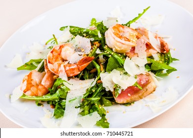 Rocket salad with shrimps on white plate