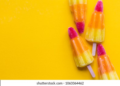Rocket shaped summer ice lolly on a bright yellow background