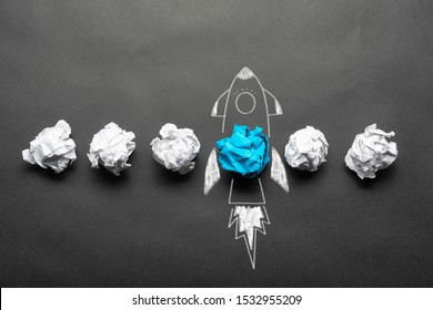 Rocket sketch drawing with crumpled blue paper ball on chalkboard. Successful business startup. Creative motivation with copy space. Unique business idea among failing ideas metaphor.