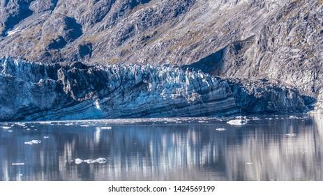 Rockface/rock face of Johns Hopkins Glacier & floating ice, Glacier Bay National Park and Preserve Alaska, a 12 mile long glacier in the tidewater inlet basin.