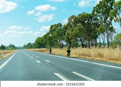 Rockhampton, Queensland, Australia - 16th September 2019: Two bicycle riders pedaling along the highway