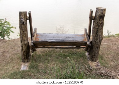 Rocking bench on the shore of a pond. Empty wooden swing on the coast.