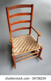 Rocking Chair: Antique shaker style rocker with woven cane seat. Photographed against gray porch floor.