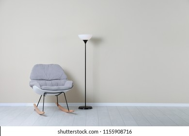 Rocking chair and lamp near color wall with space for text. Interior element