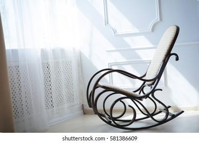 rocking chair near a sunny window light