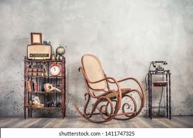 Schaukelstuhl, altes Telefon, Rundfunk, Retro-Kamera, Rahmen leer, Globus, Bücher, antike Ferngläser, Wecker, Karnevalmaske, goldener Schlüssel, Souvenirs im Regal. Vintage-gefiltertes Foto