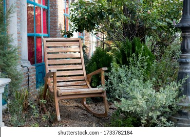 Rocking chair on pebbles in the garden,  beside the house.