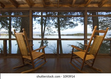 Rocking chairs on a porch looking out over the lake.