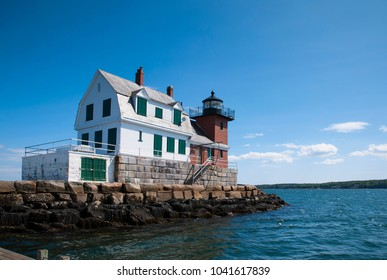 Rockland Breakwter lighthouse with its wooden building and brick tower, sits on the end of a breakwater on a summer day in Maine.