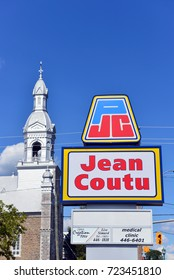 ROCKLAND, CANADA - AUG 13, 2017: Sign for Jean Coutu on Laurier St. The drug store chain has over 400 stores in Quebec, Ontario and New Brunswick..Paroisse Très Sainte Trinité church is in background.