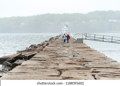 Rockland, Maine, USA - September 19, 2018: Two women heading out on the 7/8-mile walk to the Rockland Breakwater Light on a foggy morning