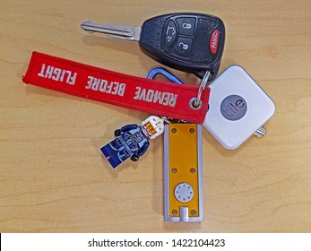 ROCKLEIGH, NEW JERSEY - MAY 9, 2019: A Tile Bluetooth tracker attached to a key chain along with a key fob, key, small flashlight, Star Wars Lego figure and a Remove Before Flight banner on a desktop.