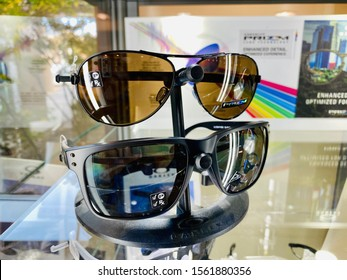 Rocklin, CA - November 16, 2019: Oakley brand sunglasses with shaded prescription lenses, displayed inside optometry office behind glass.