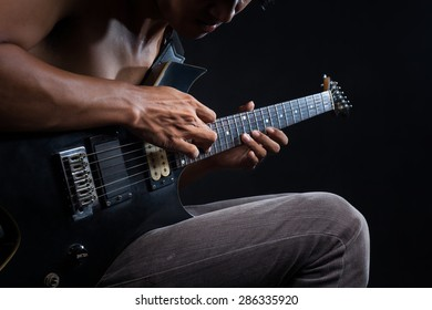 Rockman Playing Electric Guitar Close Up Photography. Hands on Guitar. Elegant Brown Color Grading.