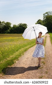 Rock'n'roll Girl with a petticoat dress and a sunshade walking on a path in the sunny nature