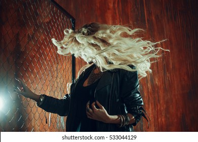 Rock'n'roll girl, young beautiful woman dances in dark alley, against the fence mesh