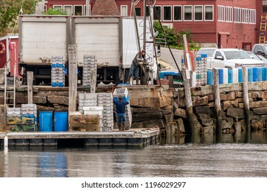 Rockport, Maine, USA - September 19, 2018: Workers dropping stacks of totes onto floating dock for transfer to lobster boat