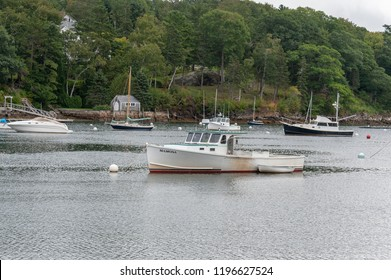 Rockport, Maine, USA - September 19, 2018: Lobster boat Mamosa   moored in Rockport harbor with skiff alongside