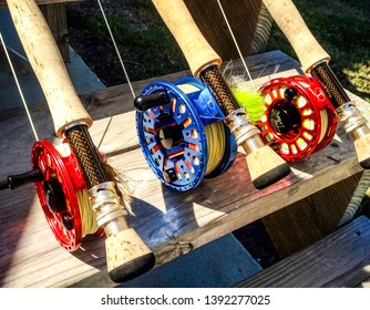Rockport, Texas USA 09-02-2012 Fy rids and reels sitting on rustic wooden steps. Rods are rigged with flies for saltwater fishing.