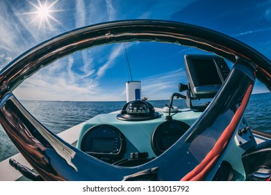 Rockport, TX / USA - 03/12/2014: Boat steering wheel ocean view like being there with blue sky & clouds, adventure on the coast