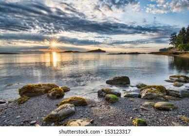 Rocks along coast with sun star