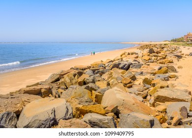 Rocks along the soft sand of the golden beach of Isla Canela beach, Andalucia, Spain on a summer day with blue sky.
