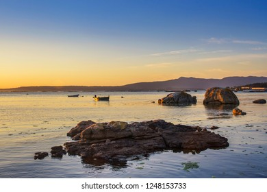 Rocks and anchored boats on the sea in Arousa Island at the evening