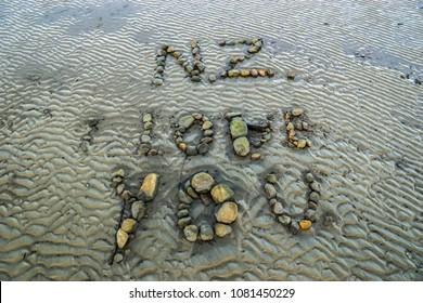 "Rocks arranged on a beach in Abel Tasman National Park to say ""NZ I love you""."