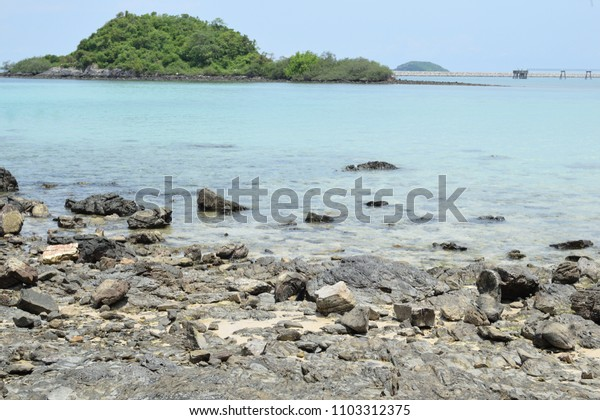 Rocks at beach with  blurred small island in sea.