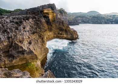 Rocks in the beautiful beach in Bali, Nusa Penida, with big waves in the blue sea. Brown rocks, grey rocks, mountains and forest, green park, it's a big island, paradise in summer with a lot of Sun.