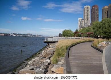Rocks between Hudson River and wooden walkway at Hudson River park, New York