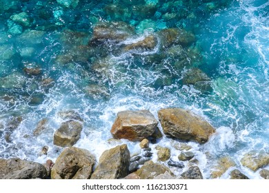 Rocks in the blue Mediterranean Sea on a bright sunny day.