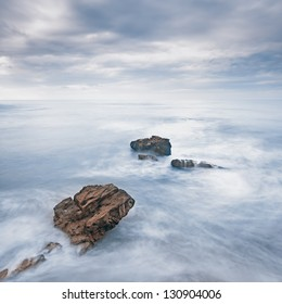 Rocks in a blue ocean waves under cloudy sky in a bad weather. Long exposure photography