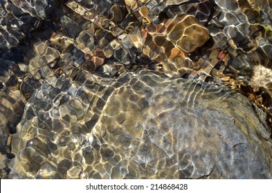 rocks at the bottom of a clear mountain stream