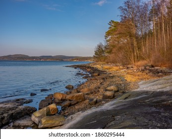 Rocks and boulders on a shore in Sweden. Warm lighting in the scen from a low setting sun.