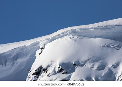 Rocks, cliffs on a mountain slope. Winter, snow and snow-pack.