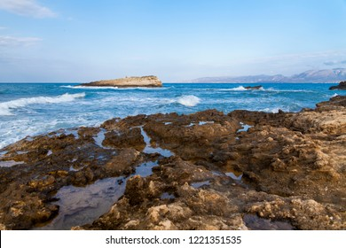 The rocks are in contact with the sea. Rocky beach, sharp rocks touching the sea, Greece island of Crete.