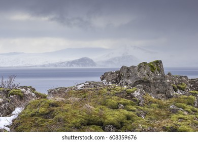 Rocks covered with moss in front of heavy clouds covering some snowy mountains and a lake.