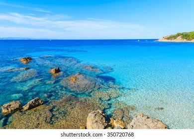 Rocks in crystal clear azure sea water in Grande Sperone bay, Corsica island, France