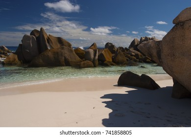 Rocks emerging from the sea in Anse Marron, La Digue, Seychelles pictured from the beach with blue sky and clouds