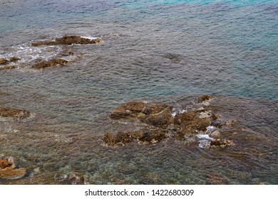 Rocks emerging from shallow water in the ocean, dangerous for boats and ships
