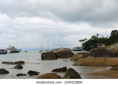 Rocks in the foreground and the scuna sailing in Ilhabela, Brazil.