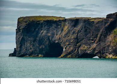 Rocks formation on Dyrholaey cape with black sand beach near  Vik town, Iceland in summer on sunny day