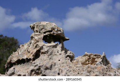 rocks in Formentera, oddly shaped, Balearic Islands, photograph of rock formations as magical beings on the coast of the island of Formentera,hippies, photographic tourism,blue sky,cliff