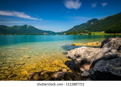 Rocks in front of the Sea in Austria called Wolfgangsee with clear water which turquoise is blue and mountains in the background and clouds in the sky