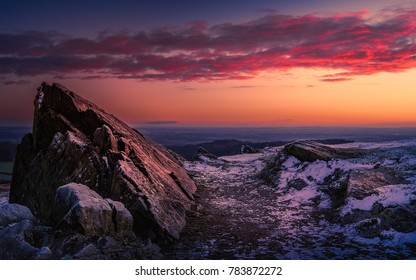 The rocks of Hunts Hill, Bradgate Park with a light dusting of snow, under pink clouds at dawn.